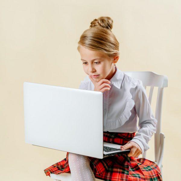 little-girl-school-age-looks-laptop-light-background-internet-addiction_119439-339